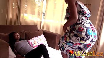 Не молодая блондиночка в кожаных штанах хвастает ступнями на беленьком диване