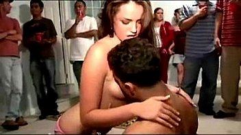 Женщина в красном юбке обнажает свое тело в домашней обстановке